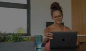 Girl in glasses looking up something on her computer